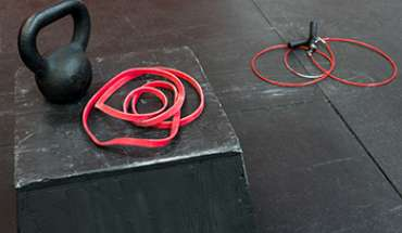 Black kettle bell and red fitness band on a black jump box, red